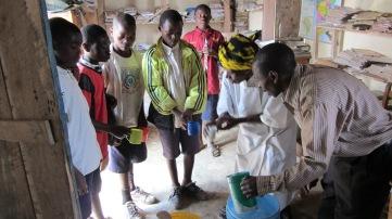 To medlemmer av Twawose som deler ut yoghurt til tålmodige elever