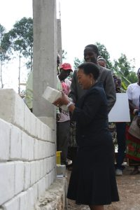 Fylkesdamen legger stein på siste muren og åpner internatet. Den stolte byggmesteren ser på i bakgrunnen