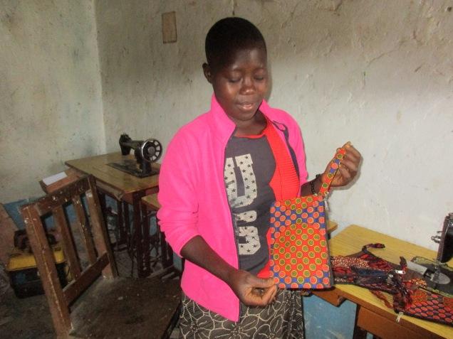 Happy, som fikk støtte av Mgetas venner til å ta yrkesutdannelse i søm og tekstil i Kibaha, er nå leder av sygruppa for unge foreldreløse kvinner. Hun viser en kaffepose av kangastoff med glidelås. Posen kan gjenbrukes som toalettveske. All kaffen vi selger er pakket i poser laget av Happy og sygruppa.