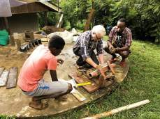 I regn og under krevende villkår har Karl Kristian laget en form til å presse piperør av leire. Michael og Simba følger med. Vi trenger å få ferdig bygget med entreprenørskapsrom i Luale